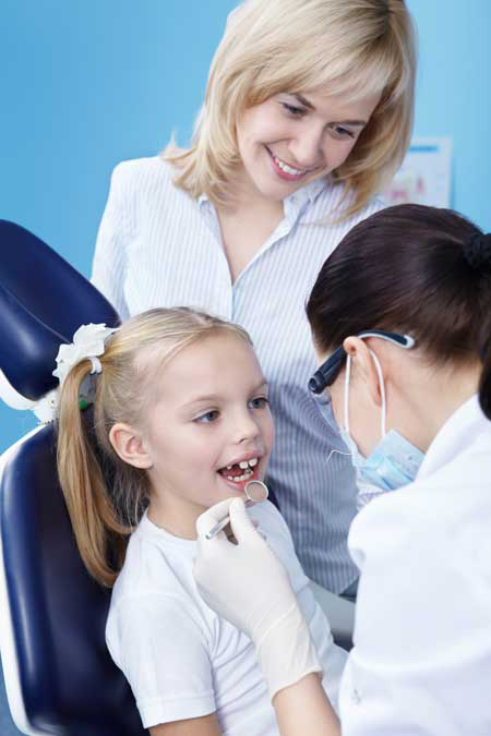 dentist examing a child in article about sedation dentistry for children